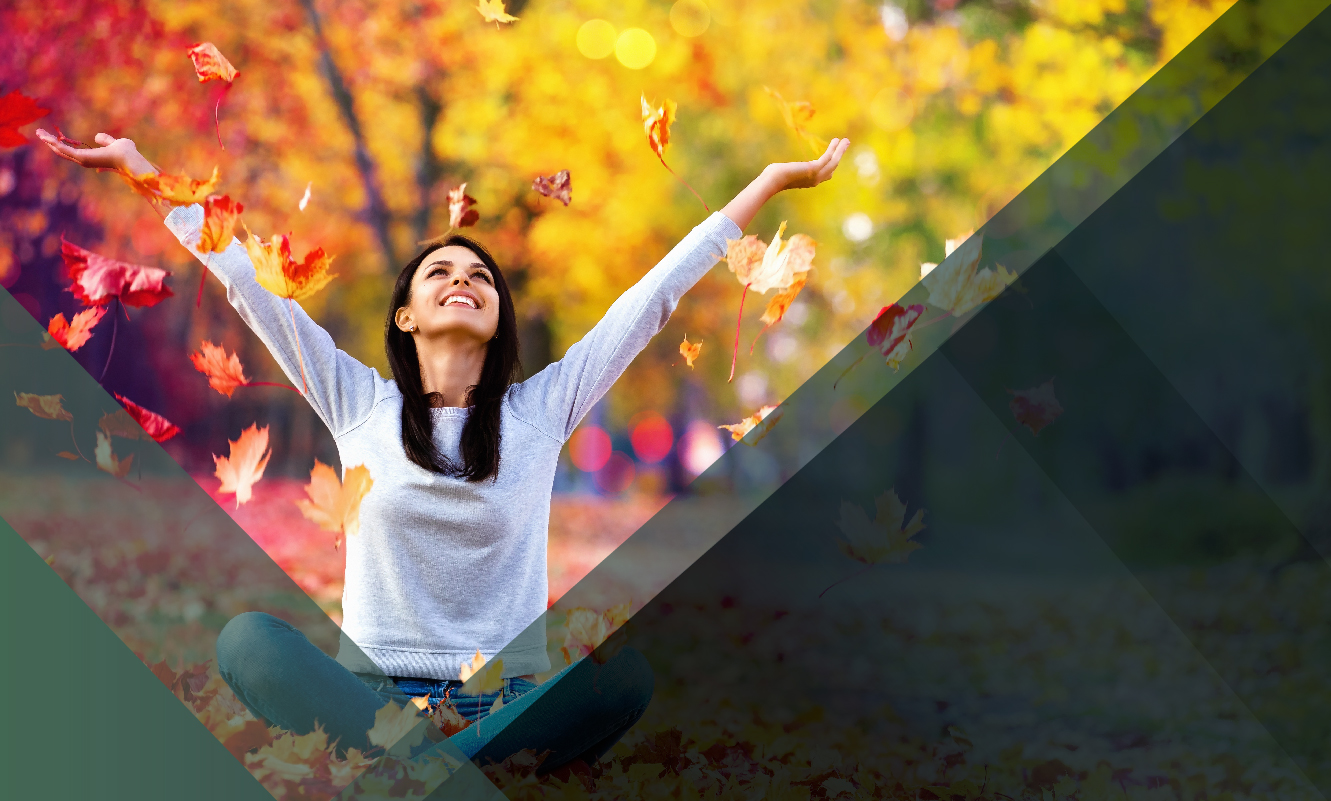 A woman sitting on the ground on a fall day hero header image